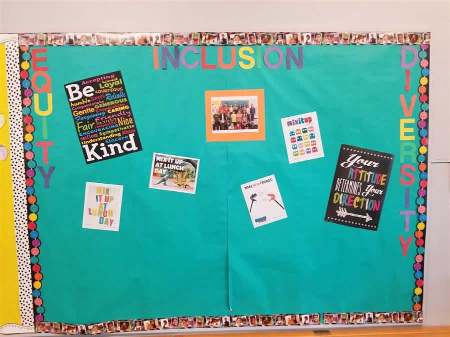 School bulletin board covered in teal paper, with the words Equity, Diversity, and Inclusion in rainbow colored letters.