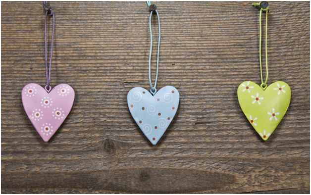 Image of a pink, yellow and blue heart hanging on a wood background